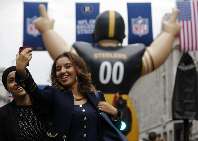 Fans take a picture of themselves with an inflatable American Football player during a 'block party' on London's Regent Street ahead of the Pittsburgh Steelers versus the Minnesota Vikings and San Francisco 49ers versus the Jacksonville Jaguars NFL matches in London September 28, 2013. REUTERS/Luke MacGregor (BRITAIN - Tags: SPORT SOCIETY)