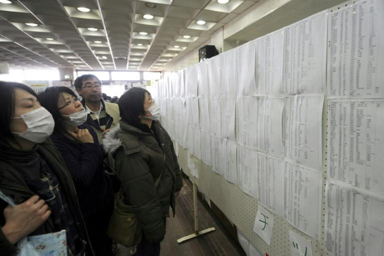 People check lists for survivors at an evacuation centre in Miyagi prefecture on March 14, 2011