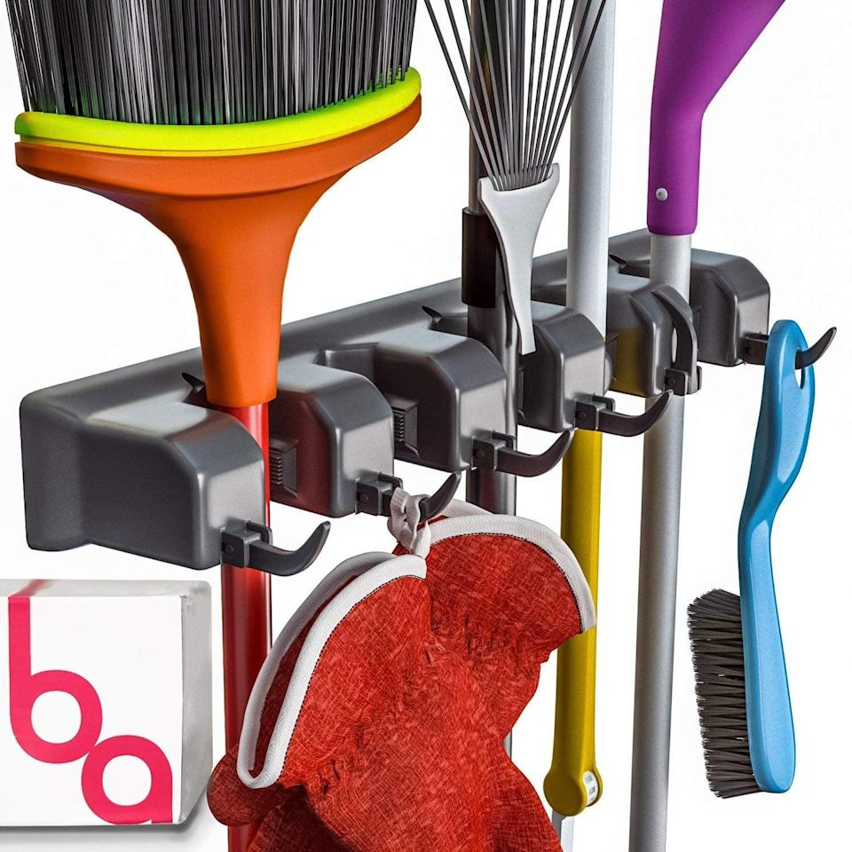 <p>Clean up your tools with this <span>Berry Ave Broom and Garden Tool Holder</span> ($15). It holds everything from a mop to a rake, and can be hung in the garage or your hall closet.</p>