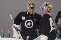 Dallas Stars goaltenders Ben Bishop (30) and Jake Oettinger (29) chat during a break in an NHL hockey practice in Frisco, Texas, Thursday, Sept. 23, 2021. (AP Photo/LM Otero)