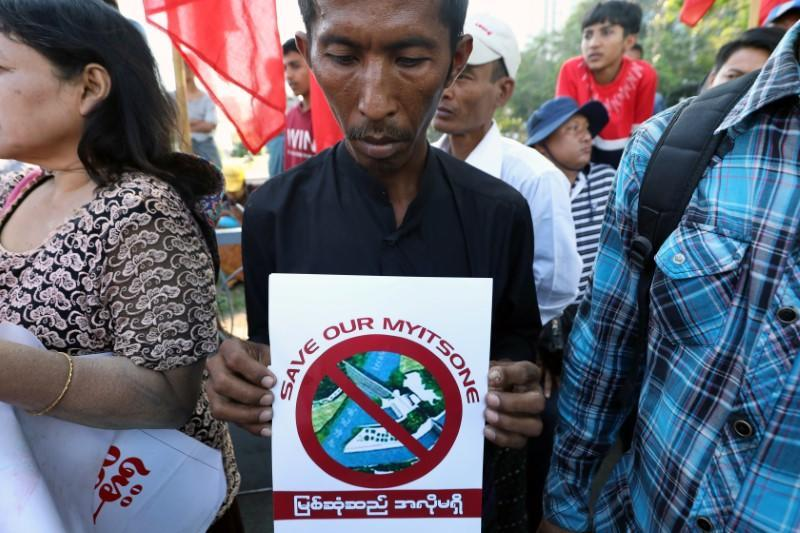 A protester holds a flyer against Myitsone hydropower dam during the last day of Chinese President Xi Jinping's visit in Yangon