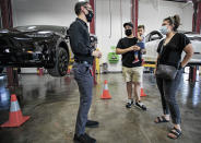 In this Sept. 9, 2021 photo, Tesla owners Joshua Vigil and Melanie Vigil, right, talk with Tesla service manager Brandon Arpin, left, during an event to celebrate a partnership between Tesla and the Nambé Pueblo after the electric car company repurposed a defunct casino into a sales, service and delivery center near Santa Fe, N.M. Tesla has opened a store on tribal land in New Mexico, sidestepping car dealership laws that prohibit car companies from selling directly to customers. (Jim Weber/Santa Fe New Mexican via AP)