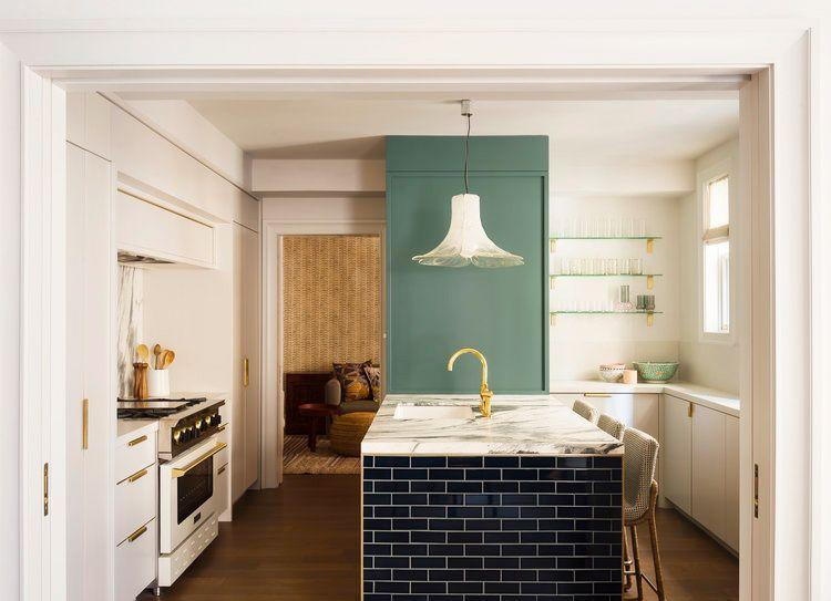 <p>Instead of painting all of the cabinets or walls, experiment with color on a statement wall. This sage green pop in a kitchen designed by Studio DB adds the perfect amount of personality. Green glass shelves and a large green bowl tie back to the unexpected color.</p>