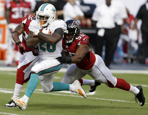 Atlanta Falcons defensive end Osi Umenyiora (50) tackles Miami Dolphins running back Lamar Miller (26) during the first half of an NFL football game, Sunday, Sept. 22, 2013, in Miami Gardens, Fla. (AP Photo/Wilfredo Lee)