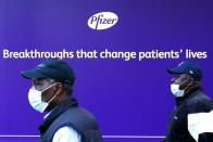 A person walks past the Pfizer Headquarters building