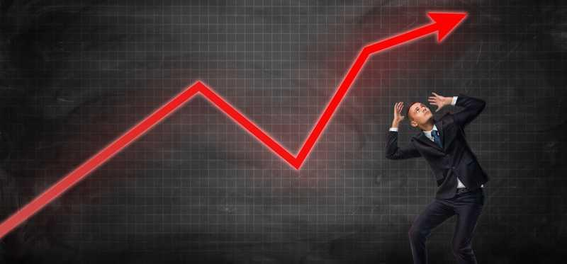 A man ducking under the a volatile line chart.