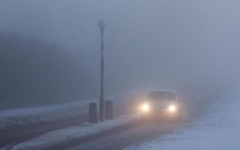 Car driving with headlights on in the fog - Credit: Alamy