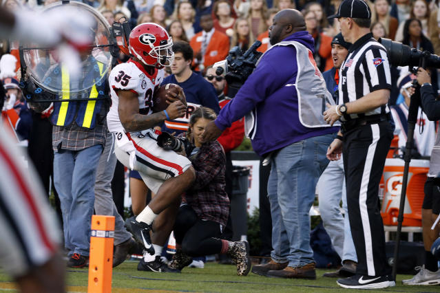 "Georgia running back <a class=""link rapid-noclick-resp"" href=""/ncaaf/players/267148/"" data-ylk=""slk:Brian Herrien"">Brian Herrien</a> (35) runs out of bounds and into a photographer during the first half against Auburn. (AP Photo/Butch Dill)"