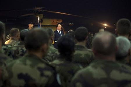 French President Francois Hollande (C) speaks with French soldiers after he paid tribute to two French soldiers who were killed overnight, in Bangui, December 10, 2013. REUTERS/Fred Dufour/Pool