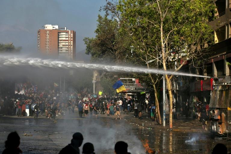 Riot police deployed water cannons in an attempt to control anti-government demonstrations in Santiago