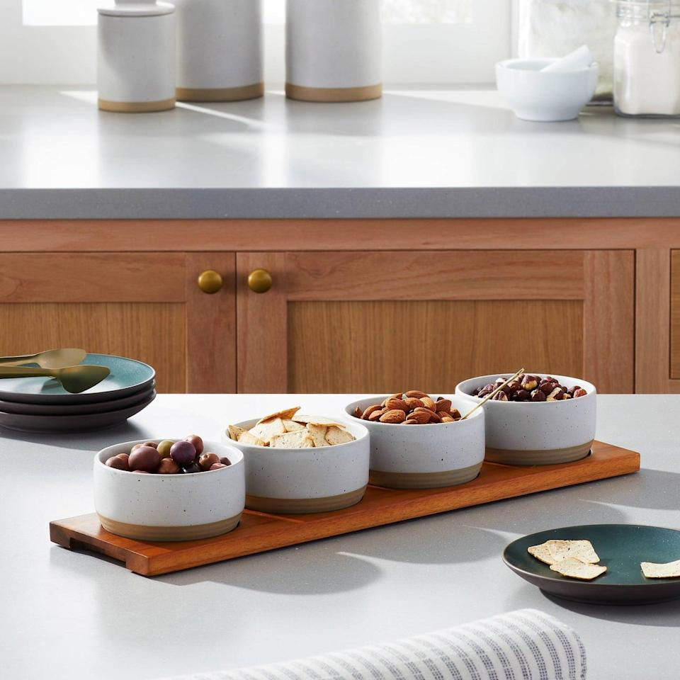 <p>Their next dinner party will require the <span>Hearth &amp; Hand With Magnolia Wood Paddle With 4 Speckled Stoneware Bowls</span> ($30). They can fill them with everything from nuts, chips, and whatever else fits.</p>