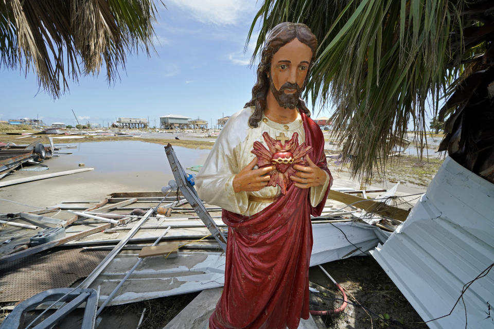 A statue of Jesus that had fallen during Hurricane Laura was uprighted by unknown persons, amid devastation in Holly Beach, La., in the aftermath of the hurricane, Saturday, Aug. 29, 2020. (AP Photo/Gerald Herbert)