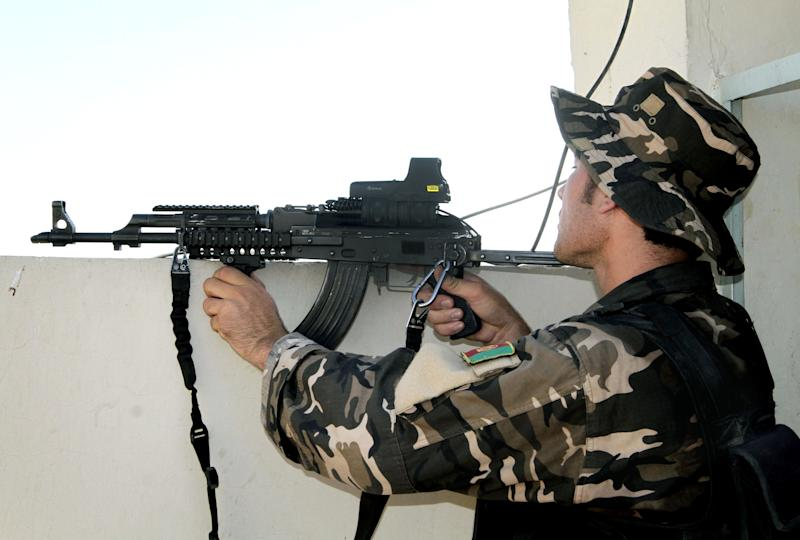 An Afghan security man aims his weapon towards Taliban militants, not pictured, during a gun battle in Kandahar, south of Kabul, Afghanistan, Monday, July 9, 2012. Three suicide bombers riding in a three-wheeled vehicle blew themselves up Monday afternoon in Kandahar city, killing two children and wounding several other civilians, said Kandahar provincial spokesman Ahmad Jawed Faisal. A short time later, three more suicide bombers tried to attack the police headquarters in Kandahar, but were gunned down by police before they could get into the compound, Faisal said. (AP Photo/Allauddin Khan)