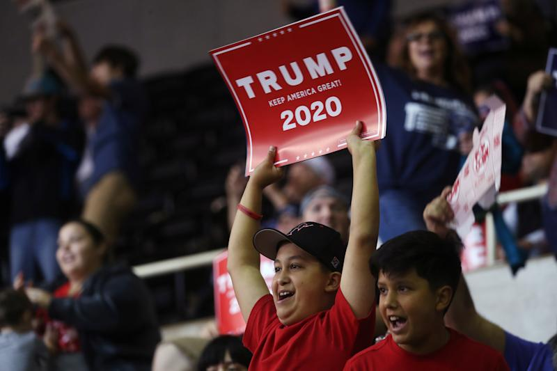 """A supporter holds up a """"Trump 2020"""" sign during a rally by U.S. President Donald Trump in Lake Charles, Louisiana, U.S., October 11, 2019. REUTERS/Leah Millis"""