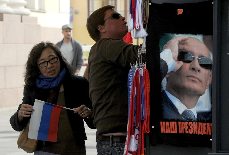 A Chinese tourist holds Russian flag as she visits a gift kiosk in St. Petersburg, on September 4, 2015 (AFP Photo/Olga Maltseva)