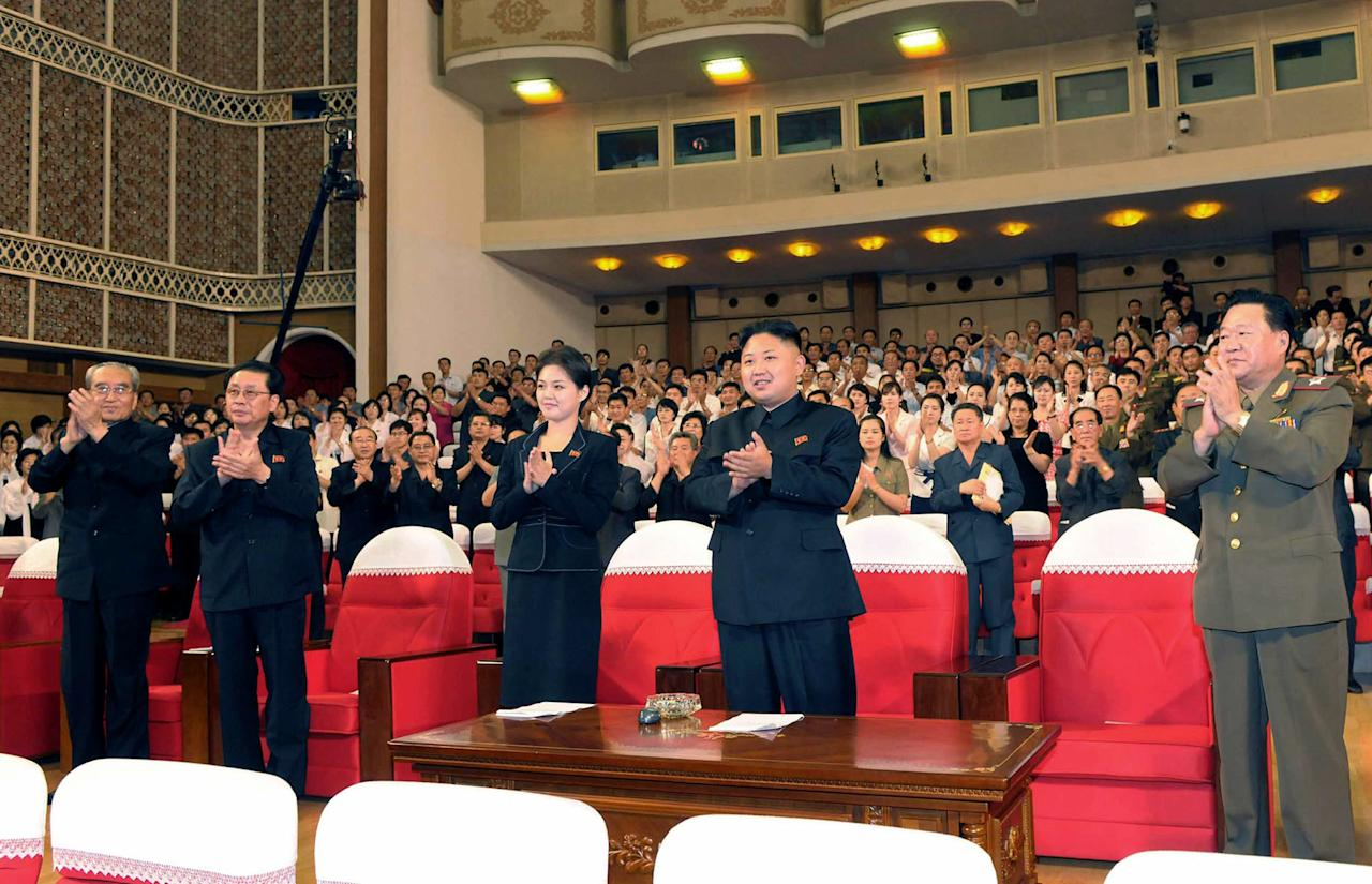 In this photo released by the Korean Central News Agency (KCNA) and distributed in Tokyo by the Korea News Service on Monday, July 9, 2012, North Korean leader Kim Jong Un, center right, and a woman clap with others as they watch performance by North Korea's new Moranbong band in Pyongyang, North Korea, Friday, July 6, 2012. The source did not identify the woman but South Korean media speculated that she could be Kim's younger sister or wife. (AP Photo/Korean Central News Agency via Korea News Service) JAPAN OUT UNTIL 14 DAYS AFTER THE DAY OF TRANSMISSION