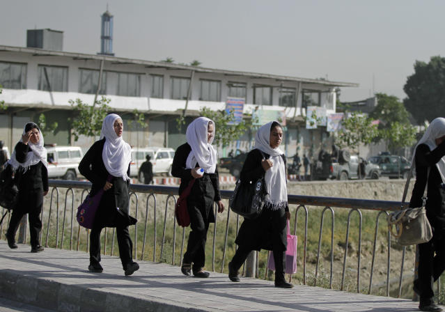 Afghan school girls walk near the entrance gate of the presidential palace after an attack by the Taliban in Kabul, Afghanistan, Tuesday, June 25, 2013. Suicide attackers blew up a car bomb and battled security forces outside Afghanistan's presidential palace Tuesday after infiltrating one of the most secure areas of the capital. The army said the attackers were killed but knew of no other deaths. (AP Photo/Ahmad Jamshid)