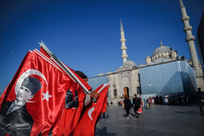 A vendor sells Turksih national flags and posters of Mustafa Kemal Ataturk, founder of modern Turkey, near a mosque at Eminonu district in Istanbul (AFP Photo/Ozan Kose)