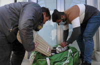 Ali Cheema, right, a former cricketer from Pakistan, helps to unpack cricket gear that was delivered to migrants in Tuzla, Bosnia, Thursday, May 20, 2021 arranged by the Rome-based humanitarian group the Baobab Experience. Among those who sought the gear and who waited eagerly for the packages to arrive was Ali Cheema, who said he started playing cricket when he was 7 and used to play for several clubs in his native Pakistan. Now 24, Cheema has been in Bosnia for the past two years. (AP Photo/Kemal Softic)