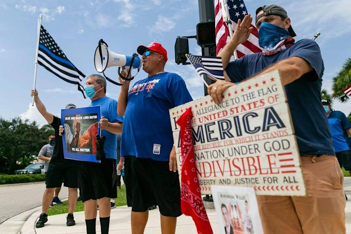 Ricky Dee, 40, center, and Seth Feder, 40, right, both Coral Springs residents, attend a Back The Blue rally near Marjory Stoneman Douglas High School in Parkland, Florida on Saturday, July 11, 2020.