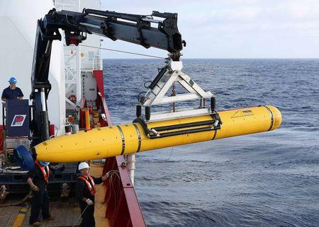 Crew aboard the Australian Defence Vessel Ocean Shield move the U.S. Navy's Bluefin-21 autonomous underwater vehicle into position for deployment in the southern Indian Ocean to look for the missing Malaysia Airlines flight MH370 April 14, 2014 in this file handout picture released by the U.S. Navy. Malaysia on August 28, 2014 said it would share with Australia the cost of the latest effort to uncover signs of the missing flight MH370, in the hope of unlocking modern aviation's greatest mystery. REUTERS/U.S. Navy photo by Mass Communication Specialist 1st Class Peter D. Blair/Handout via Reuters/Files