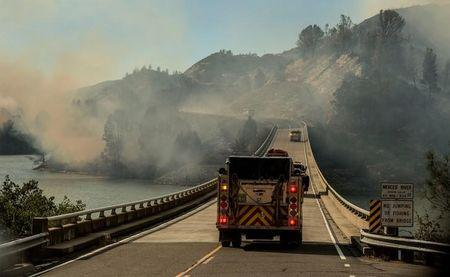 A firetruck drives across the Merced River at the Bagby bridge after authorities ordered evacuations due to the Detwiler fire in Mariposa, California, U.S. July 18, 2017. REUTERS/Al Golub