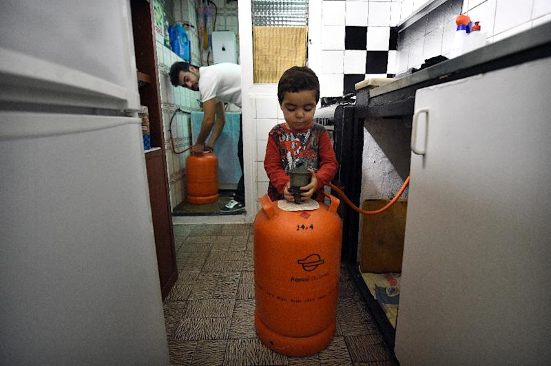 Mohamed Chairi and his two-year-old son Badder change a butane gas bottle in their home in Badalona, Spain (AFP Photo/Lluis Gene)
