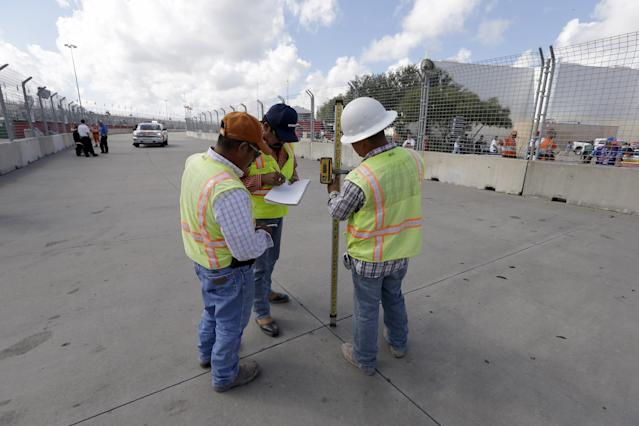 Workers check the track elevation at the IndyCar Grand Prix of Houston auto race, Friday, Oct. 4, 2013, in Houston. Practice and qualifying was delayed due to a surface issue in turn one. (AP Photo/David J. Phillip)