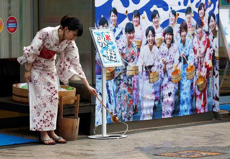 A woman wearing a Yukata or summer kimono splashes water onto the hot asphalt in an old Japanese tradition called Uchimizu ritual meant to cool down the air as the water evaporates outside a pachinko game parlor in Tokyo