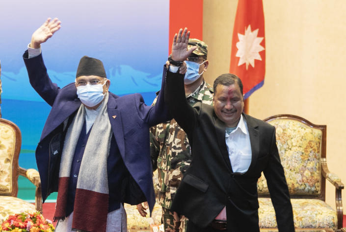 Nepalese Prime Minister Khadga Prassad Oli, left, and leader of Nepal Communist Party group Netra Bikram Chand raise their hands during a signing of peace agreement in Kathmandu, Nepal, Friday, March 5, 2021. Chand, who is better known by his guerrilla name Biplav, emerged out of hiding on Friday after the government lifted a ban on his group so it could take part in the public signing of the peace agreement. This group had split from the Maoist Communist party, which fought government troops between 1996 and 2006, when it gave up its armed revolt, agreed to U.N.-monitored peace talks and joined mainstream politics. (AP Photo/Niranjan Shrestha)