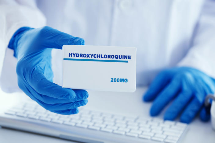closeup of a man, wearing a white coat and blue surgical gloves, having a simulated box of hydroxychloroquine in his hands