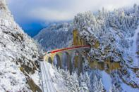 <p>A train passing through the Landwasser Viaduct in the Alpine village of Filisur, part of the canton of Graubünden in Switzerland.</p>