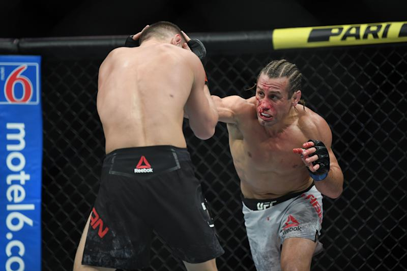 Dec 14, 2019; Las Vegas, NV, USA; (Editor's Note: Graphic Content) Petr Yan (red gloves) fights Urijah Faber (blue gloves) during UFC 245 at T-Mobile Arena. Mandatory Credit: Stephen R. Sylvanie-USA TODAY Sports