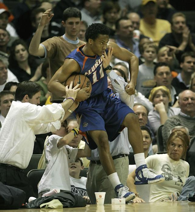 FILE - In this Feb. 15, 2006, file photo, Florida guard Taurean Green gets some help from the fans to keep from falling into the crowd while playing Vanderbilt in the second half of a college basketball game in Nashville, Tenn. Oklahoma State All-American guard Marcus Smart is serving a three-game suspension for shoving a fan who later apologized for his actions. The incident shows how volatile the interaction between fans and athletes is becoming. (AP Photo/Mark Humphrey, File)