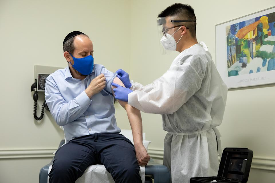 ROCKVILLE, MD - JULY 27: Rabbi Shmuel Herzfeld has his arm disinfected by Dr. Chao Wang during a clinical trial for a Coronavirus vaccine at Meridian Clinical Research in Rockville, Maryland on Monday, July 27, 2020. The Coronavirus vaccine was created by the biopharmaceutical company Moderna. (Photo by Amanda Andrade-Rhoades for The Washington Post via Getty Images)