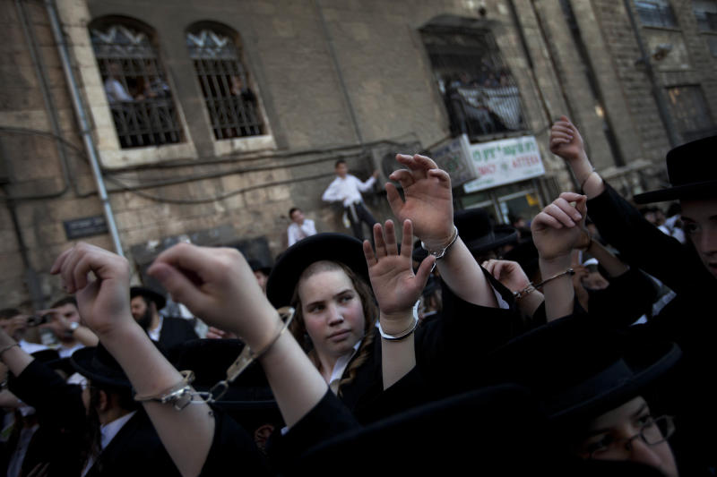 Handcuffed Ultra Orthodox Jewish children participate in protest against attempts to draft members of the cloistered community into the Israeli military, in an ultra Orthodox neighborhood in Jerusalem, Israel, Monday, July 16, 2012. Thousands of ultra-Orthodox Jews, including hundreds of children, are protesting against attempts to draft members of the cloistered community into the Israeli military. The government is currently trying to find a formula to obligate ultra-Orthodox Jews to serve in the military before a court-determined Aug. 1 deadline. ? The current law largely exempts the community from military service. That infuriates many Israelis, since almost all are required to serve. Israel's Supreme Court ruled the law must be revised. (AP Photo/Oded Balilty)