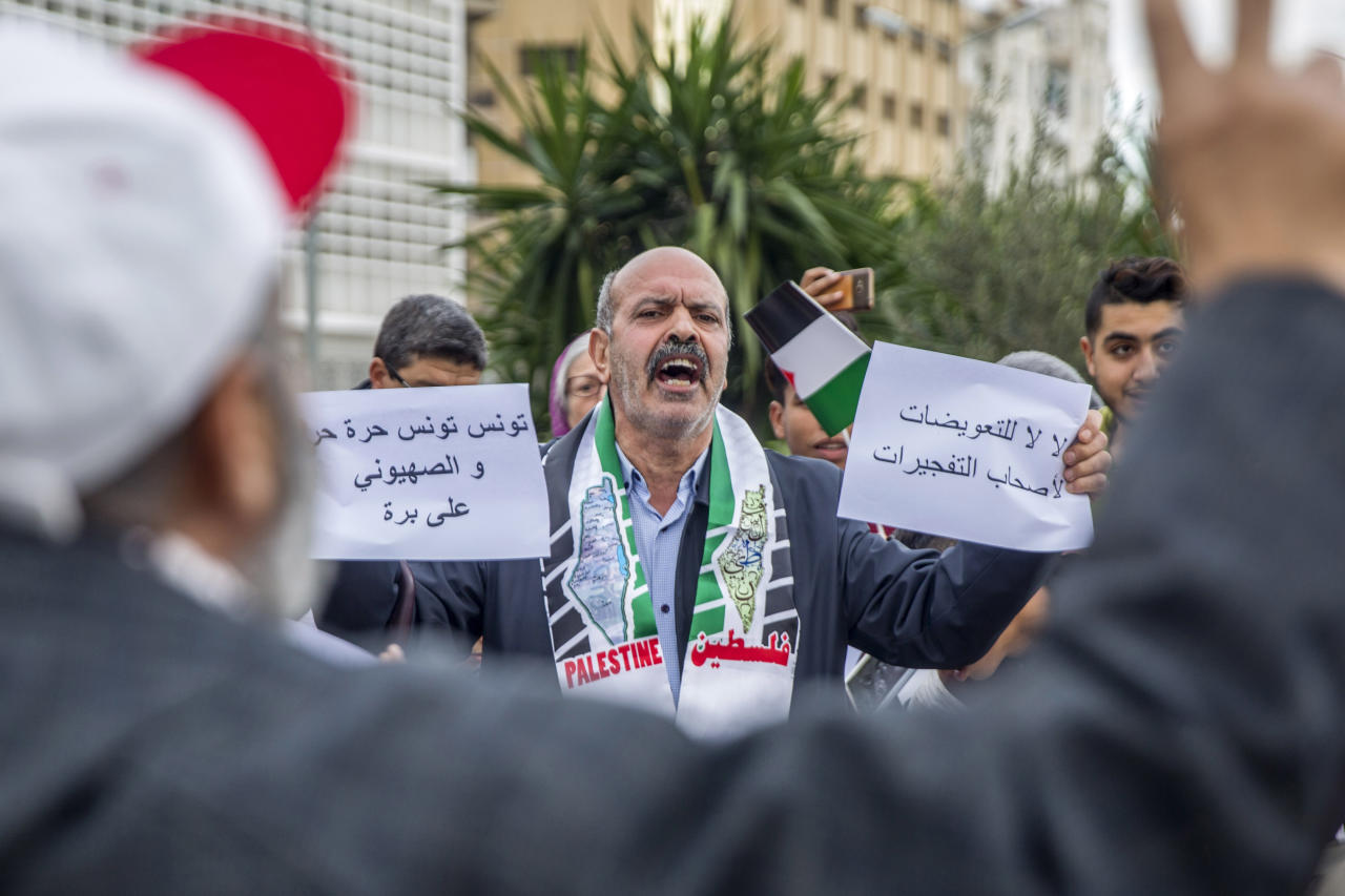 "A Tunisian holds anti-Israel posters reading ""Tunisia is Free, Sionists out"" outside the Tunisian Tourism Ministry in Tunis, Saturday, Dec.8, 2018. Rene Trabelsi, a Jew, has been recently named Tunisian tourism minister, a first in more than 50 years. (AP Photo/Hassene Dridi)"