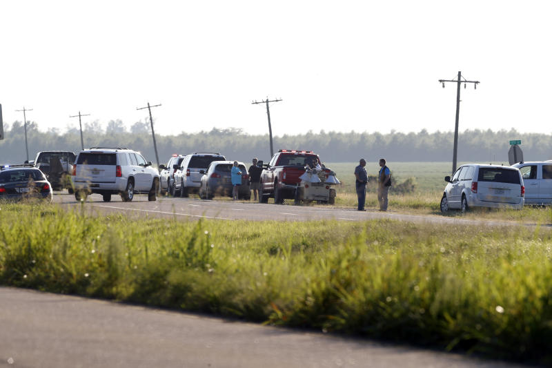 Emergency personnel stand along U.S. Highway 82 after a military transport plane crashed into a field near Itta Bena, Miss., on the western edge of Leflore County, Monday, July 10, 2017. Several were killed in the crash. (AP Photo/Andy Lo)