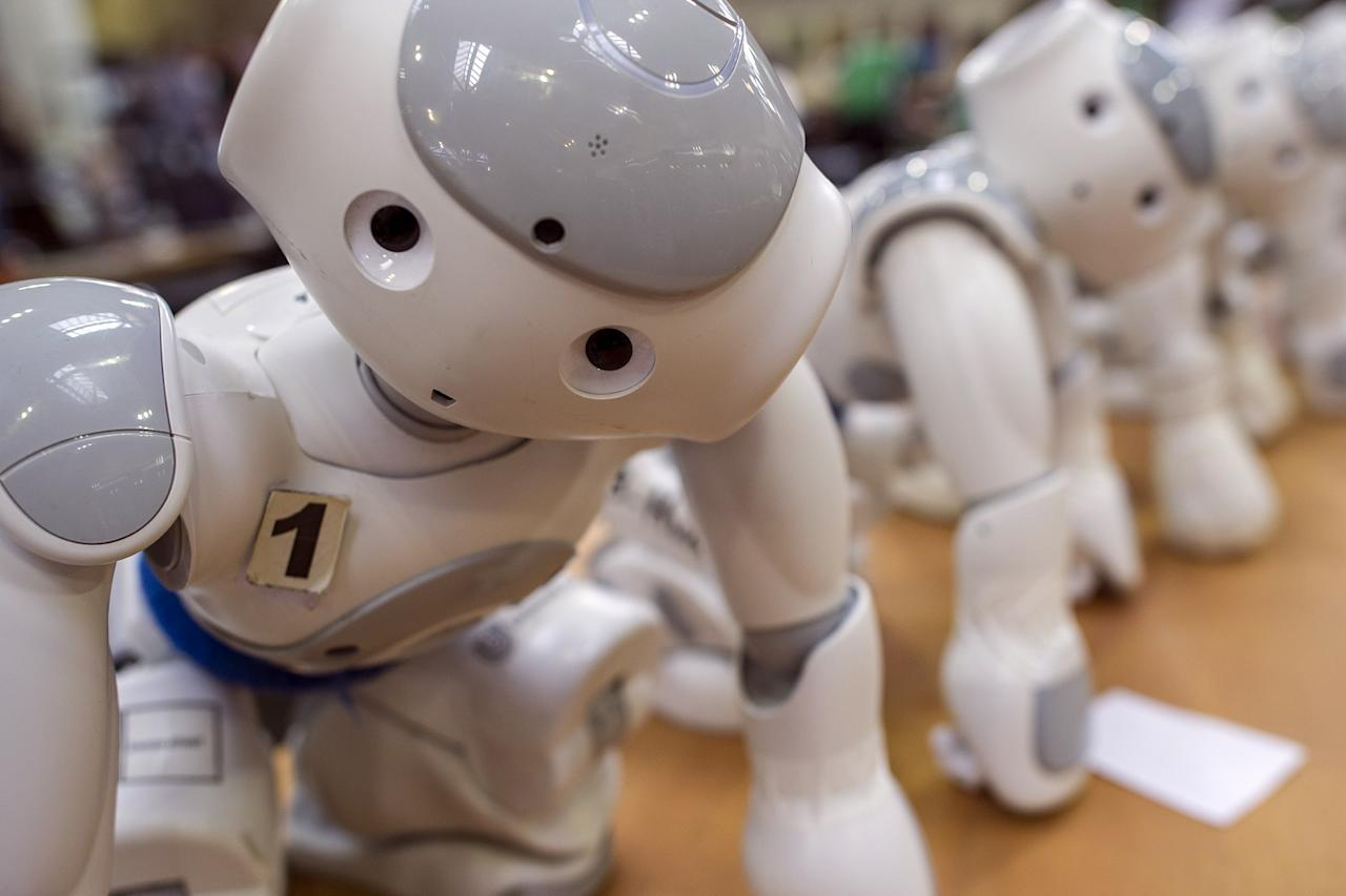 MAGDEBURG, GERMANY - APRIL 26:  Robots stand at a table near the play field at the 2013 RoboCup German Open tournament on April 26, 2013 in Magdeburg, Germany. The robots, which are a model called Nao, manufactured by Aldebaran Robotics, perform autonomously and communicate with one another via WLAN. The three-day tournament is hosting 43 international teams and 158 German junior teams that compete in a variety of disciplines, including soccer, rescue and dance.  (Photo by Jens Schlueter/Getty Images)