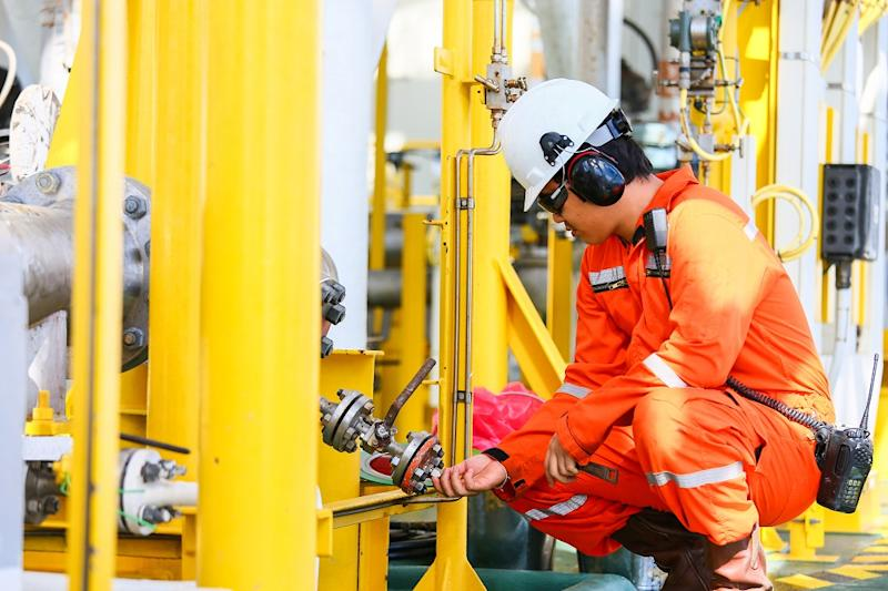 Worker installing a part on an oil rig.