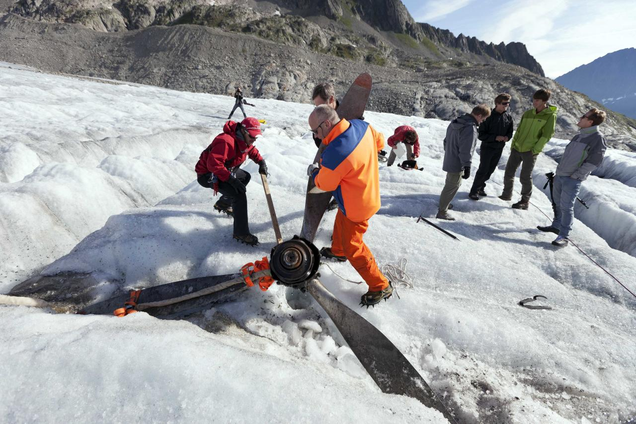 "Mountain rescuers recover the propeller of US warplane C-53 Skytrooper ""Dakota"" that crashed in 1946, on the Gauli glacier in the Bernese Alps, Switzerland, Thursday Aug. 9, 2012. Three young climbers discovered a propeller piece of the legendary airplane at the end of July 2012. The Dakota crash on the Gauli Glacier on Nov. 19, 1946 was a turning point in alpine rescue and an international media event. The aircraft, coming from Austria bound for Italy, collided with the Gauli glacier in poor visibility. On board were four crew members and eight passengers. Among the eight passengers were high-ranking officers of the U.S. armed forces with some of their relatives. Several people were injured, but there were no fatalities. The propeller will be transported to the near Gauli cabin. (AP Photo/Keystone, Gaetan Bally)"