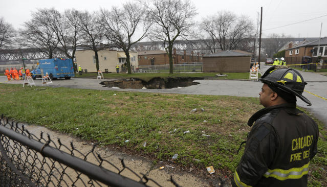 Officials survey a gaping sinkhole that opened up a residential street on Chicago's South Side after a cast iron water main dating back to 1915 broke during a massive rain storm Thursday, April 18, 2013, in Chicago. The hole spanned the entire width of the road and chewed up grassy areas abutting the sidewalk. Two of the cars that disappeared inside had been parked, but a third was being driven when the road buckled and caved in. Only the hood of one of the vehicles could be seen peeking from the chasm.(AP Photo/M. Spencer Green)