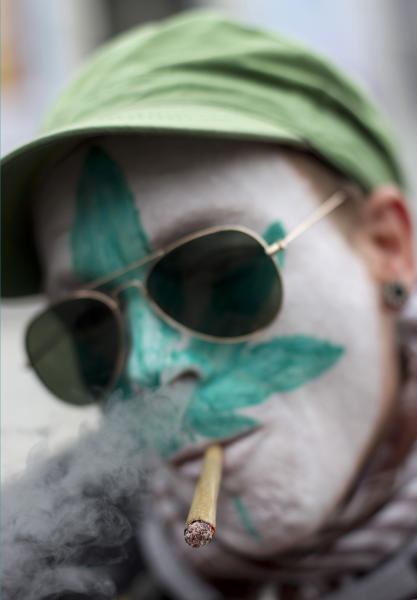 FILE - In this Friday April 20, 2012 file photo a protestor from Belgium with a marijuana leaf painted on his face smokes a marijuana joint in Amsterdam during a protest against a government plan to stop foreigners from buying marijuana in the Netherlands. The owners of three cannabis-selling cafes in Maastricht, southern Netherlands, went on trial Wednesday in the southern Netherlands charged with selling weed to foreigners, in a case both sides of a heated drugs debate in this border city hope will clarify the legality of a clampdown on so-called coffee shops. Maastricht is using new legislation banning coffee shops from selling cannabis and marijuana to people who don't live in the Netherlands as a way of clamping down on what the local mayor says was nuisance caused by hundreds of thousands of drug tourists driving into the picturesque heart of the city to stock up on weed. (AP Photo/Peter Dejong, File)