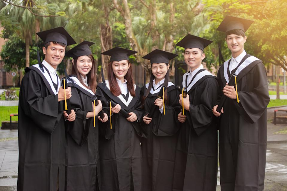 Group of young university students with graduation gowns feeling excited and pride posted for a group photo
