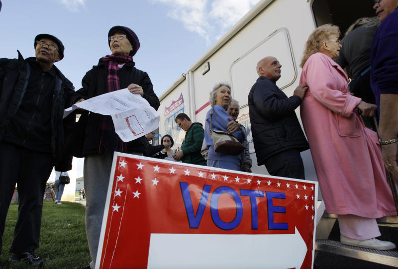 Tj Cheng and his wife Quin Wang of East Windsor, N.J., stand together Monday, Nov. 5, 2012, in Burlington, N.J., outside a Mobile Voting Precinct, as they inquire about voting. Many victims displaced by Superstorm Sandy are taking advantage of offers to vote early. (AP Photo/Mel Evans)