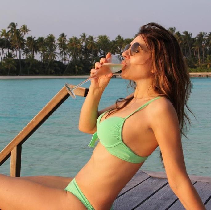 Liz Hurley drinks champagne in a bikini by the water