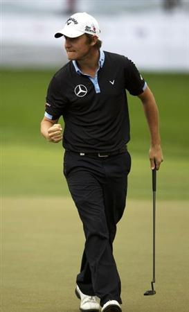 Grillo from Argentina pumps his fist after scoring an eagle on the 18th hole to briefly take the lead in the final round of the 2014 Omega Dubai Desert Classic in Dubai