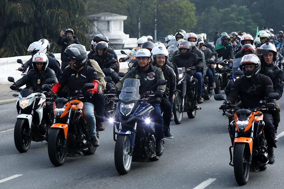 SAO PAULO, BRAZIL - JUNE 12: President of Brazil Jair Bolsonaro (C) rides a motorcycle during a motorcycle rally through the streets of Sao Paulo on June 12, 2021 in Sao Paulo, Brazil. (Photo by Rodrigo Paiva/Getty Images)