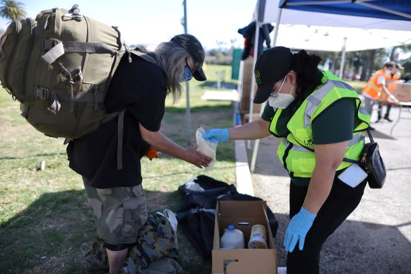 A woman hands out food at a Los Angeles Food Bank distribution, as the coronavirus disease (COVID-19) continues, in Los Angeles