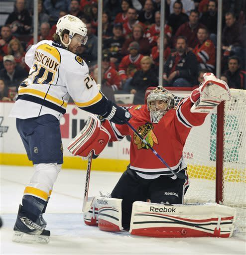 Nashville Predators' Matt Halischuk (24) tips the puck past the Chicago Blackhawks' Corey Crawford to score during the first period of an NHL hockey game on Friday, April 19, 2013, in Chicago. (AP Photo/Jim Prisching)